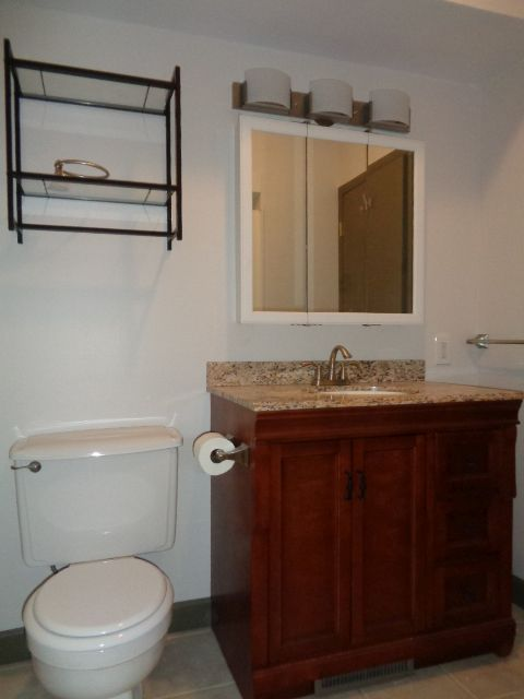 """Full bathroom 6' 6"""" x 7' 10"""" features a new all wood vanity, vanity top and recessed sink."""